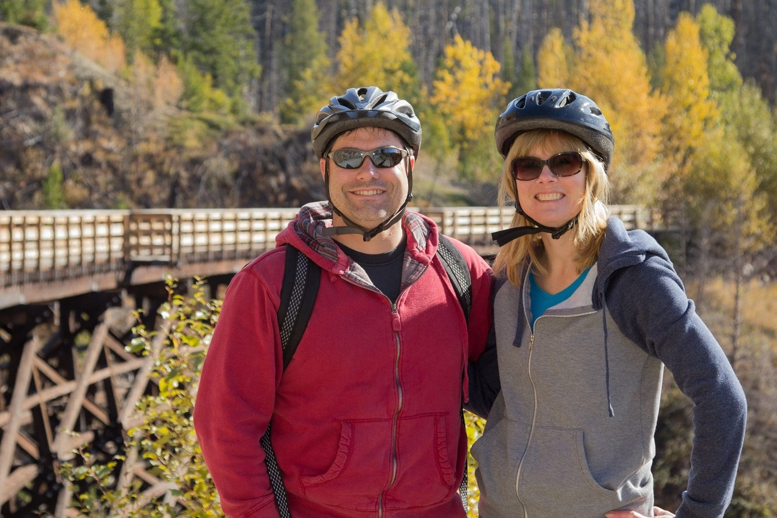 male and female couple in biking gear standing in front of myra canyon trestles high end real estate Kelowna